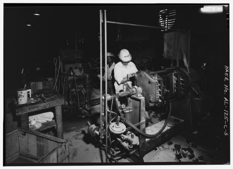 File:BEARDSLEY AND PIPER (BandP) CORE BLOWING MACHINE. VIRGINIA BLAKELY MANUALLY FILLING SAND MAGAZINE THAT WILL ROTATE WITH THE CORE BOX, FILLING IT UNDER PRESSURE SIMILAR TO THE CORE HAER ALA,37-BES,5C-3.tif