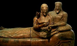 A sculpture of a woman and man reclining together on a couch, their upper bodies to the right and their legs to the left. There is a marked contrast between the high relief busts of their upper bodies and the very flattened lower bodies and legs. They have almond-shaped eyes and long braided hair, and are smiling widely. The man has a beard that is bobbed. The woman's hands are gesticulating in front of her as if she was holding something that is no longer there, or perhaps gesturing while speaking. The man has his right arm draped around the woman's shoulders in an intimate pose, and his right hand on her shoulder also appears to once have held some item. His left hand rests palm up in the crook of the woman's left elbow.
