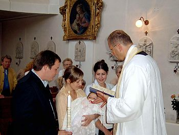 English: A Roman Catholic priest baptizes an i...