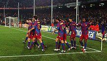 des joueurs de football se congratulent dans un stade