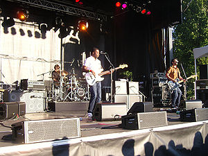 "Backline (stage) - Canadian band Bedouin Soundclash performing. The backline gear, including an 8x10"" bass speaker cabinet, drums, and several powerful guitar amps, can be seen behind the two musicians in the front of the stage."
