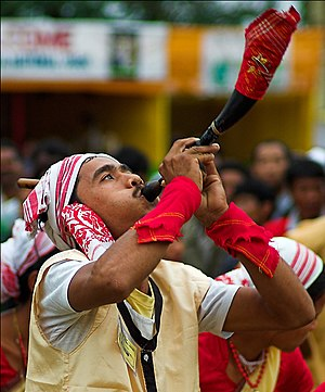 A Bihu dancer blowing a pepa (horn) Bihu dancer with a horn.jpg