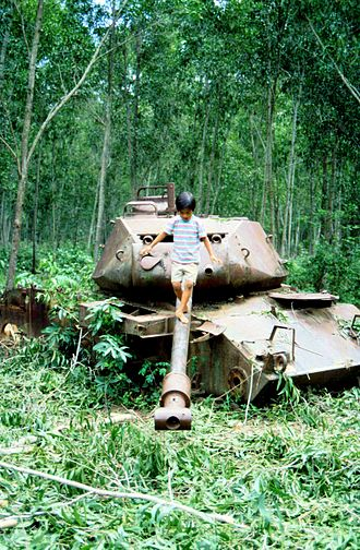 Debris - A child plays on an abandoned tank outside Phnom Penh, Cambodia in 1991