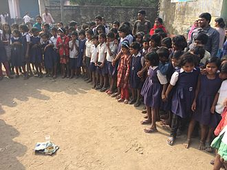 Fecal–oral route - School children during a CLTS triggering event in West Bengal, India looking at a glass of water and fresh human feces where the flies pass from the water to the feces and back. This demonstrates how water can get polluted with pathogens.