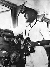 A middle-aged man wearing a white uniform and cap, holding binoculars while looking out a window