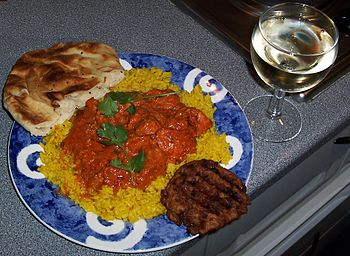 Chicken Tikka Masala served with naan bread, a...