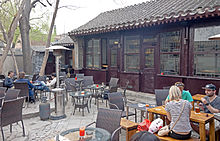 A courtyard surrounded by a high stone wall with a Chinese-style dark brown building at the rear. Within the courtyard are tables and chairs; people are seated and drinking beer at a few of them.