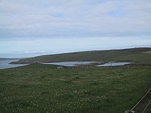 The site of The Howe of Hoxa broch (at left), Earl Thorfinn's supposed burial place Dam of Hoxa - geograph.org.uk - 931822.jpg