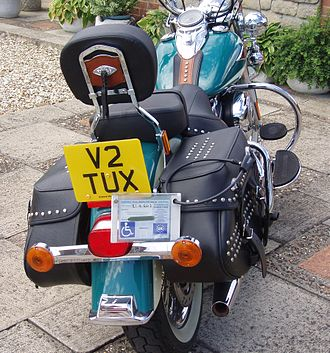 "Disabled parking permit - A UK ""Blue Badge"" Disabled Parking Permit in a custom permit holder for motorcycles, beside the license plate."
