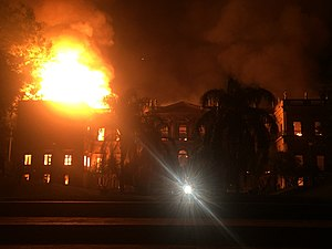 Photograph of the same building smoldering under a massive blaze, the black smoke filling the night sky