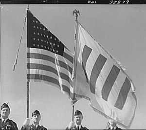 United Nations Honour Flag - 1943 photo of U.S. soldiers flying the U.S. flag and the Honor flag