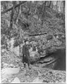 Frances Benjamin Johnston, full, standing by wooded cliff at entrance to Mammoth Cave LCCN2006688466.jpg