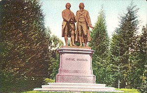 "Picture postcard of a large bronze statue of two men on top of a stone pedestal. The pedestal has the engraved words ""Goethe. Schiller."" on its front face. The statue is surrounded by tall trees. There is printing along the bottom of the postcard that says, ""1671 - Goethe Schiller Monument, Golden Gate Park, San Francisco, California"" printed along the bottom."