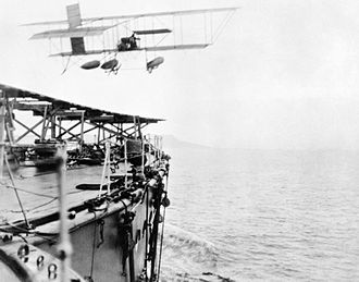 "Royal Naval Air Service - Commander C Samson of the RNAS takes off from HMS Hibernia in his modified Shorts S.38 ""hydro-aeroplane"" to be the first pilot to take off from a ship underway at sea."
