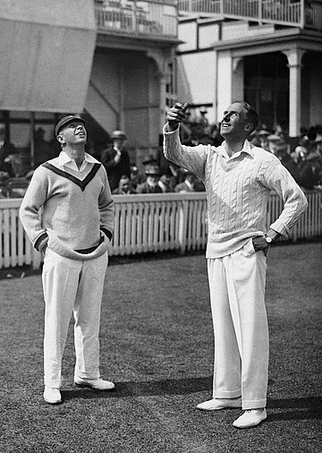 Photograph of Gilligan on the right, in front of fans, tossing a coin watched by South African Herbie Taylor on the left
