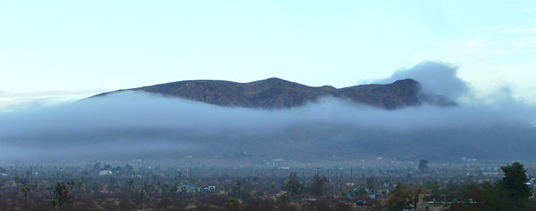 Fog, in the form of a cloud, descends upon a High Desert community in the Western United States, while leaving the mountain exposed. High Desert Fog.jpg