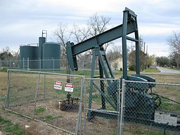Photo shows a dark gray oil pump jack from a few yards away. A cylindrical oil tank is in the background.