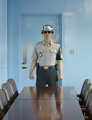 Joint Security Area - A Republic of Korea soldier of the United Nations Command Security Battalion stands guard inside a JSA conference room, in front of the door leading to the North Korean side of the JSA. View from south to north.