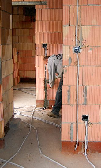 "Electrical wiring - Installing electrical wiring by ""chasing"" grooves into the masonry structure of the walls of a building"