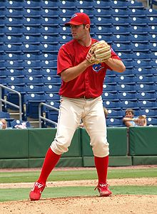 A young man wearing a red baseball jersey and cap and white baseball pants