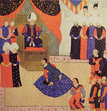 A bearded young man on his knees before a bearded old man who wears a turban and sits on a throne in a tent