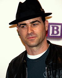 A black-haired man wearing a black fedora, a black leather jacket and a green T-shirt.