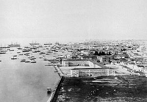 Konak, İzmir - General view of Konak Square (1865), with the Ottoman casern Sarıkışla (the Yellow Casern) and the yet unused landfill in the foreground, and the governor's residence, the square and the ships at the quay in the background