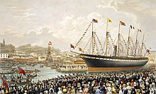 A crowd of people watch a large black and red ship with one funnel and five masts adorned with flags