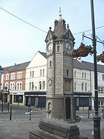 A tower-like structure in stone with a clock face on each side.  Above each clock is a gable and at the summit of the structure is a spire.