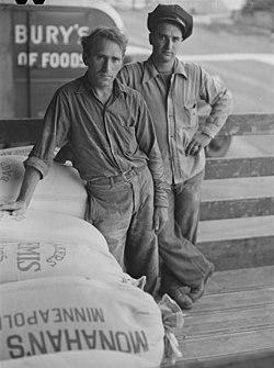 """Två män som lastade mjöl och en mjölsäck varpå det står """"Monahan s Minneapolis and Pillsbury tryck"""""""