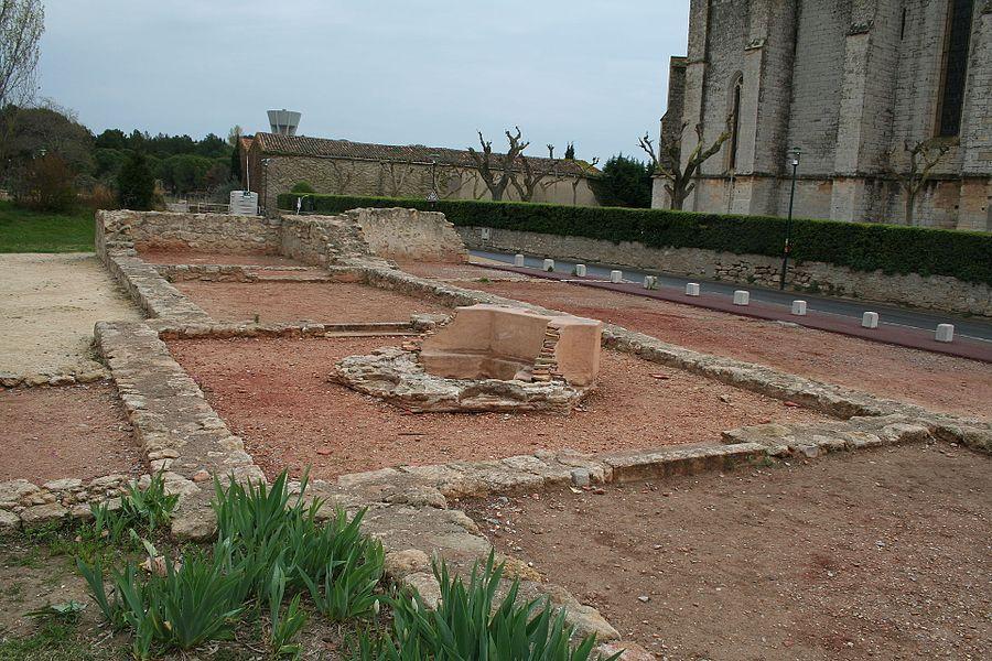 Loupian (Hérault) - église paléochrétienne (moitié de nef visible) et baptistère. L'autre moitié de la nef est située sous la route. L'actuelle église Sainte-Cécile est visible de l'autre côté de la route.