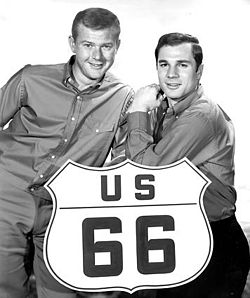 Black-and-white (greyscale) photo of blond-haired man at the left of the U.S. Route 66 large sign and black-haired man at right