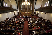 Six political candidates sit behind a short desk in a church. People fill up most of the pews in the church, and a lone microphone sits in the middle aisle.