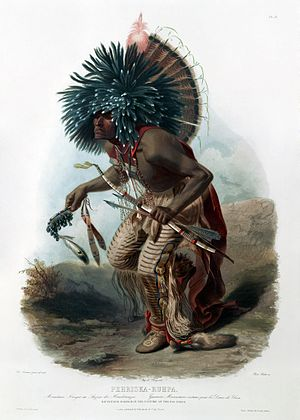 Hidatsa - Hidatsa performing dog dance in regalia by Karl Bodmer. In his right hand, he holds a rattle of pronghorn hoofs. A bone flute is hanging in a string around his neck.