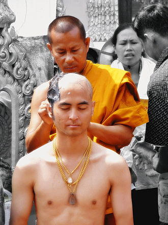Head shaving - A Buddhist monk shaving the head of a devotee to prepare him for priesthood.