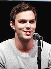 A young, Caucasian man with short, dark hair and facial stubble wearing a grey, V-neck jumper speaks into a microphone against a black background.