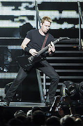 A blonde man wearing a dark T-shirt and dark jeans playing a guitar on a stage.
