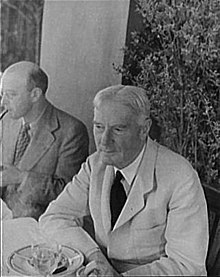 outdoor photograph of elderly man sitting at a table; he has white hair, and is clean shaven