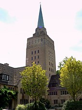 A tall light-coloured stone square tower with a small metal spire; to the left, a smaller building in the same stone with a dark tiled roof