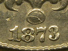 "A closeup of part of an 1873 Shield nickel; the arms of the ""3"" curve only slightly towards each other"