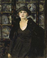 Dame in Schwarz vor einer Vitrine
