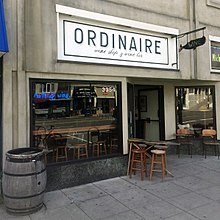 "The exterior of Ordinaire. There is a barrel, a small table with stools, and a small sign with the word ""wine"" on it in the shape of a whale"