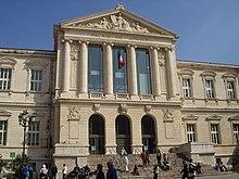Vue d'un palais de justice avec fronton et colonnes.
