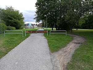 Path of least resistance - Bicycle traffic barrier used to slow down cyclists circumvented by a detour on the lawn, thereby showing a literal path of least resistance.