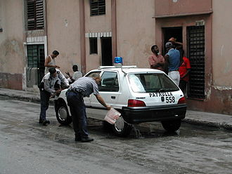 Crime in Cuba - A Cuban police car getting washed in Havana, Cuba (May 2002).