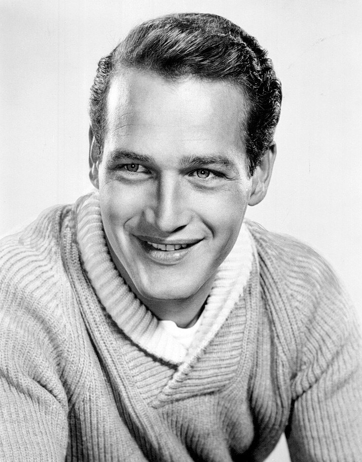 Black-and-white photo of Paul Newman in 1958—a 33-year-old man with light eyes, broad shoulders, smooth dark hair brushed to the side and a thin nose, wearing a long light-colored shirt.
