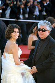 In the photo, a Caucasian male and a Hispanic female can be seen. The female has short medium brown hair and is wearing a white sleeveless dress. She is smiling and titling her head to look to her right. The male has light and dark grey hair and is wearing an all black long sleeved suit with black sunglasses. In the background, there are people standing with camera's.