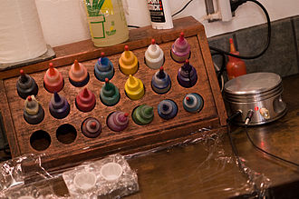 Process of tattooing - A variety of inks at a station in a tattoo shop. The small paper cups on the counter are used for mixing inks.