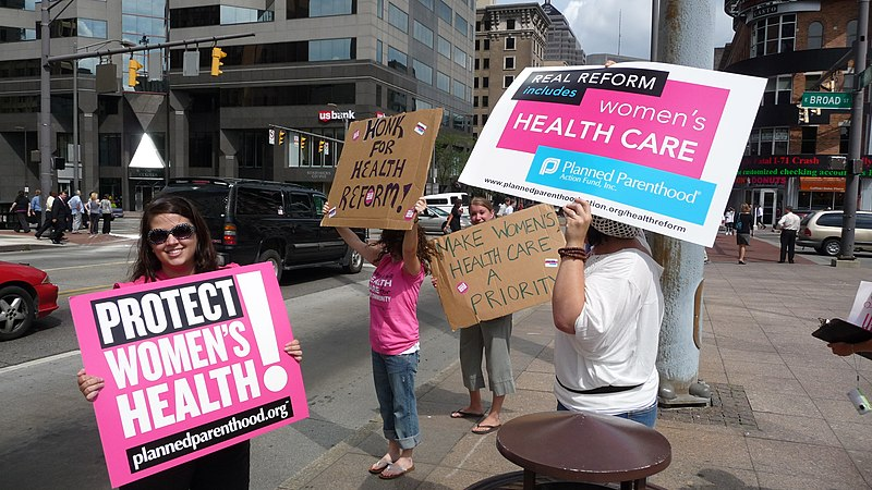 People stand on a street corner holding signs supporting choice and Planned Parenthood. A young woman smiles at the camera with a large sign reading