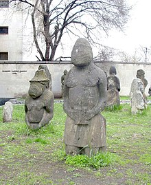 Large rude stone statues depicting men and women